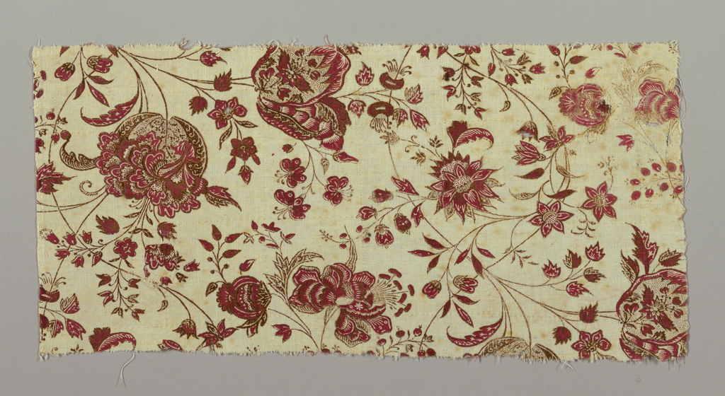 Fragment of cream-white cotton, hand-woven, block-printed in red and brown; design of flower sprays intertwining on very thin much carvd stems. Flowers show Indian influence in drawing and are printed with much interior desgin, of fine picotage in both red and brown. Flowers mainly red, with details in white of ground. Stems and outlines brown.