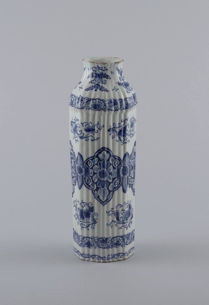 Tall reeded 8-sided body, bulge at shoulder, tapered neck, slightly flared mouth; painted in underglaze blue on white with large stylized lotus leaf band around center, 3 smaller scroll bands surrounding, and floral/leaf sprays interspersed.