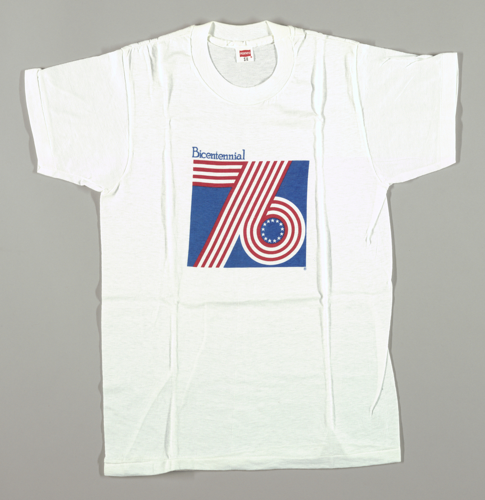 """White t-shirt with square in front center. In the center of the square is a red and white stripe '76 enclosed in a blue field. In the circle of the six are 13 small white stars. Above the square on the left side is """"Bicentennial"""" in blue letters."""