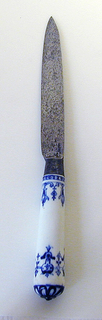 Leaf-shaped blade, almost straight edges, plain bolster. Silver ferrule with horizontal bands. Tapering white porcelain handle with dark blue floral and scrolled decoration. Silver button cap at the top of the handle.