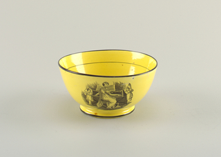 Yellow bowl with depiction of a family at piano-forte in black; black lines around rim and foot.