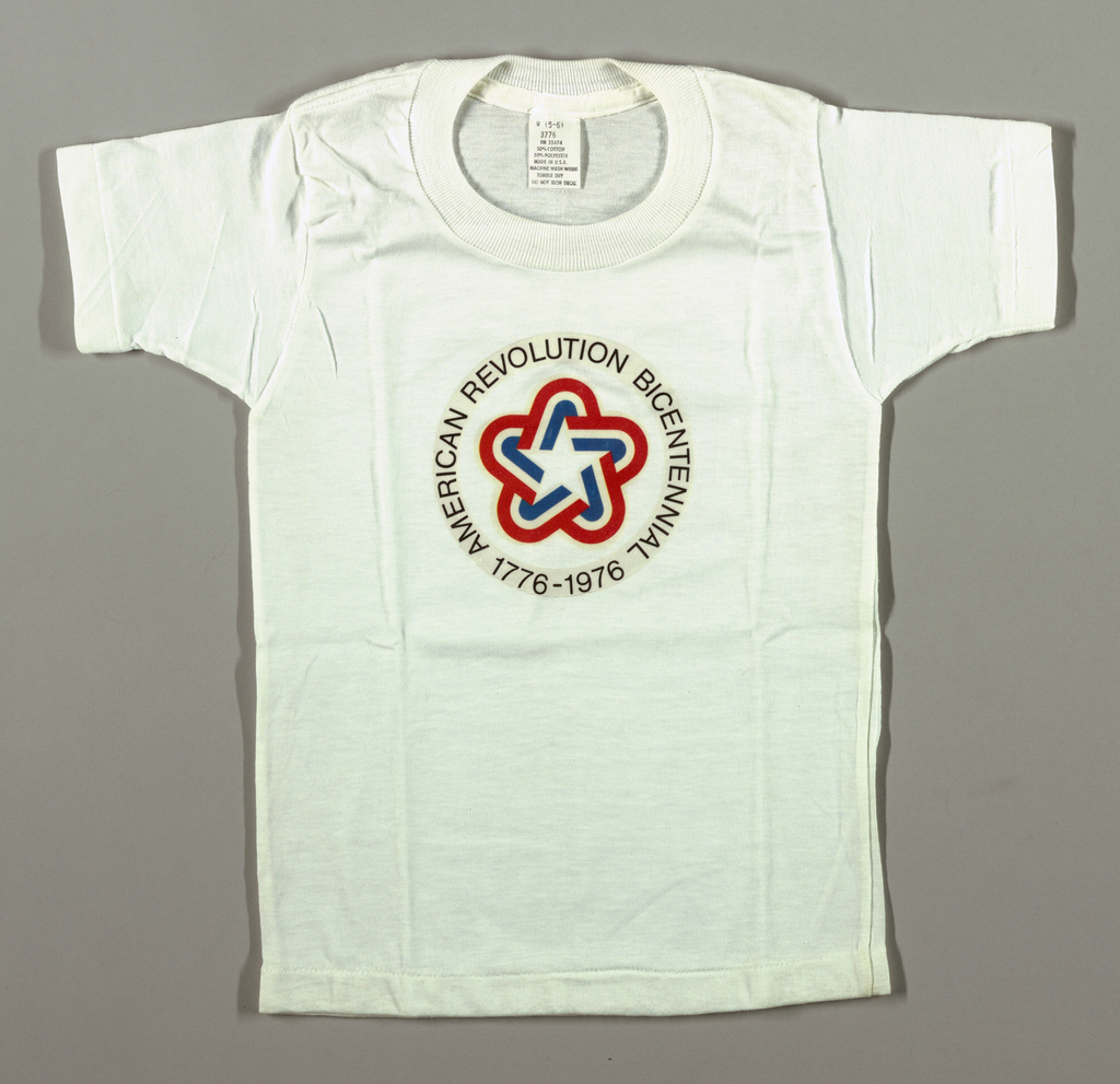 """White t-shirt with circular decal logo in front center. The logo is the official Bicentennial symbol. On the outside of the circle are the words """"American Revolution Bicentennial `776-1976."""" In the center of the circle is a rounded interlaced red, white and blue stripe star."""