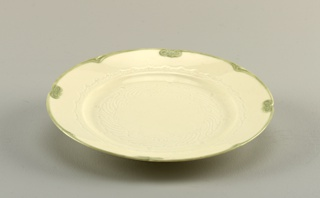 "Molded plate is circular with broad rim. Rim punctuated by 4 indentations and a knot-like device creating a scalloped profile, alternating with four ""v"" shaped devices. This motif is picked out in soft underglaze green. Center of plate molded with stylized tendril-like motif, and encircled by continuous scroll band, all molded in relief."