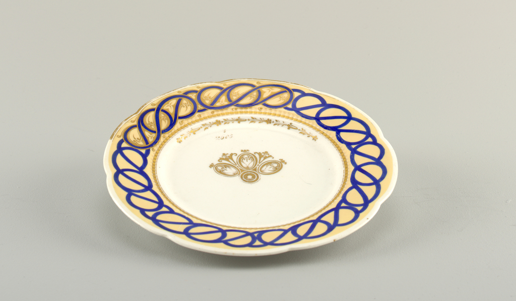 """Circular plate, the white body showing progressive sections of decoration around the scalloped rim: a tan ground with applied interlaced curving blue bands, and gilt floral border; the well with a section of gilt, stylized floral decoration in the center; the gilt numbers """"6"""" over """"2605"""" written above the decoration."""