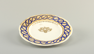 "Circular plate, the white body showing progressive sections of decoration around the scalloped rim: a tan ground with applied interlaced curving blue bands, and gilt floral border; the well with a section of gilt, stylized floral decoration in the center; the gilt numbers ""6"" over ""2605"" written above the decoration."
