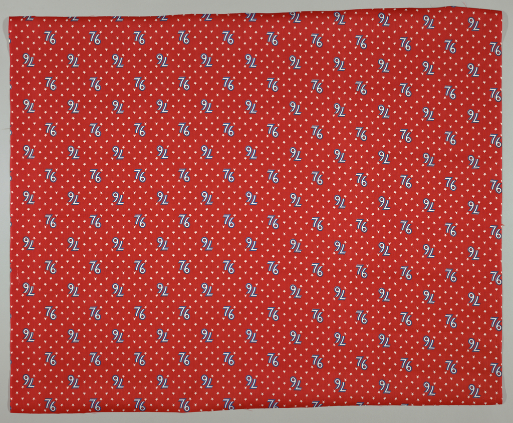 """Printed fabric commemorating the U.S. Bicentennial. """"76"""" in blue and white horizontally offset on an allover pattern of stars on a red background. Alternate rows of '76 up-side-down."""