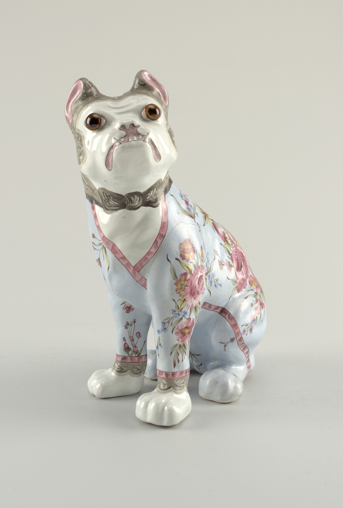 Bulldog sitting on haunches, decorated as if wearing light blue dressing gown, banded in red and embellished with predominantly red flowers, a few blue forget-me-nots and green foliage.  Painted black lace cap on head tied under chin, black lace protruding from sleeves of gown above white front paws; applied glass eyes.  Body predominantly fine red clay with some cream colored clay.