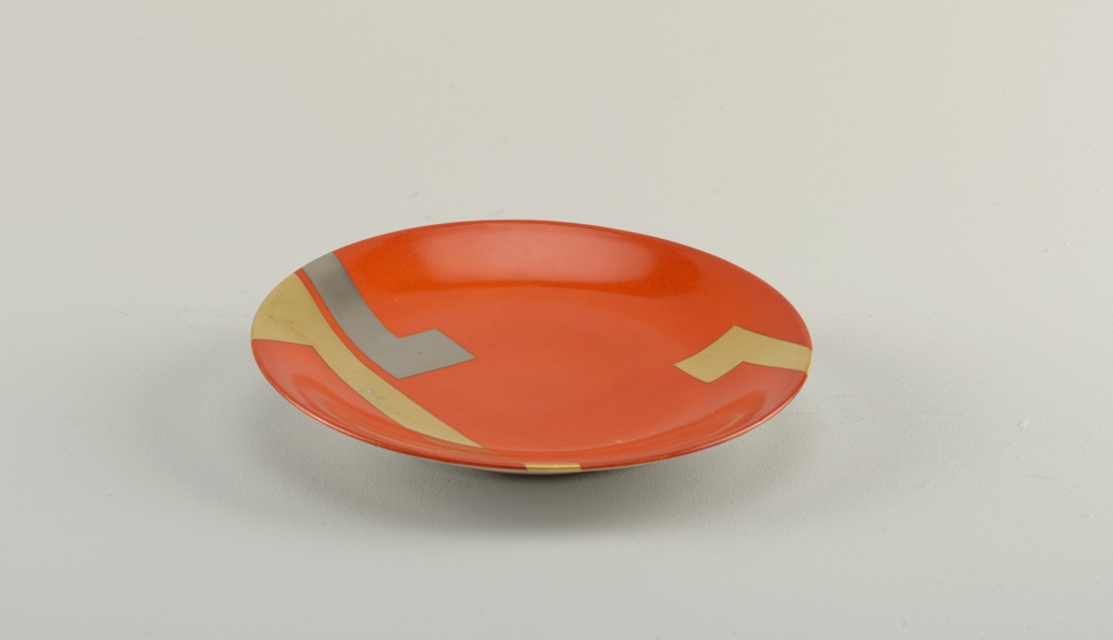 Round plate with orange-red enamel ground on front, and with two wide L-shaped gilded bands and one wide L-shaped motif in platinum.