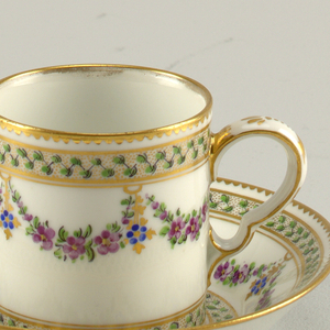 A porcelain cup and saucer with floral swags and gilding.