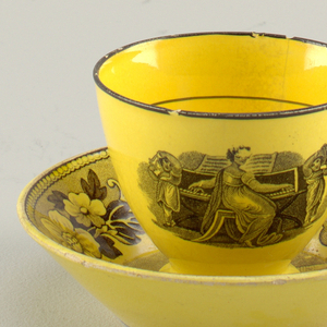 Yellow cup and saucer with black transfer images. Cup depicting a lady playing a piano. Saucer with flared sides, interior with allover floral motif.