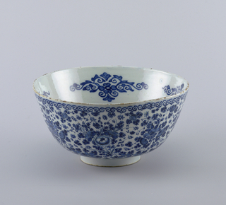 Deep circular bowl with flaring sides on short foot rim; painted in underglaze blue on white, on outside with overall floral pattern between scroll bands top and bottom; on inside with central circular panel of floral pattern, scroll border, stylized floral/scroll motifs interspersed along walls.