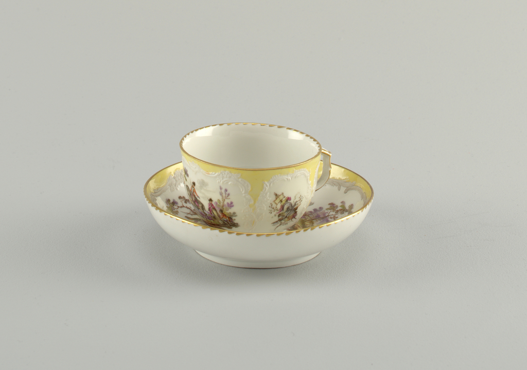 Curving cup. Slightly compressed in lower part. Scrolling handle placed in a wide panel. Military scene opposite handle, and flower under it. In narrow panels, two trophies. Saucer identical to that of 1953-17-53.