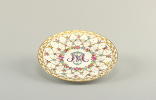 "White porcelain plate decorated with crisscross pattern of gold and floral rinceau. Well framed by colorful flowers, and ""M"". Plate bordered by gilt pattern of spades."
