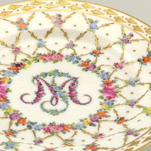 """White porcelain plate decorated with crisscross pattern of gold and floral rinceau. Well framed by colorful flowers, and """"M"""". Plate bordered by gilt pattern of spades."""