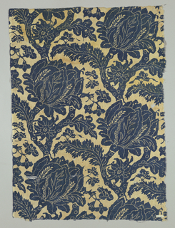 Coarse cream-colored cotton printed in one shade of blue. Design shows heavy flower heads, a serrated pointed leaf; and other smaller flowers springing on short stems from branches. Design is much enhanced by lines of white dots, particularly in outlining leaves on larger flower head.