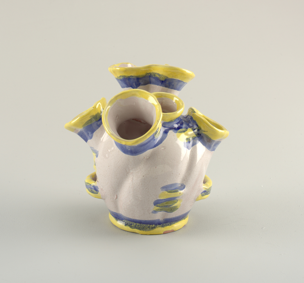 Round vessel with flat bottom. Six flaring cylinder openings with yellow and blue glaze at rim.