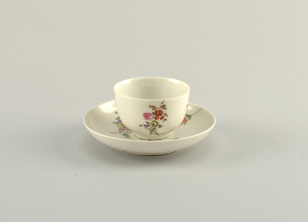 Cup has no handle; slight cylindrical base. Saucer curved. Both decorated with four sprays of flowers, on a grayish body.