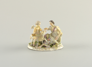 Figural group; a cherub with a grown on one arm rides a lamb to a seated female.