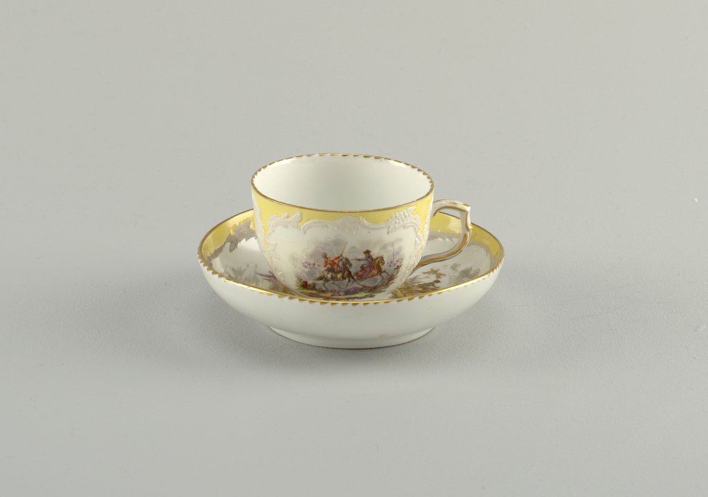 Curving cup. Slightly compressed in lower part. Scrolling handle. Saucer slightly curved. Decoration identical to that of 1953-17-50.