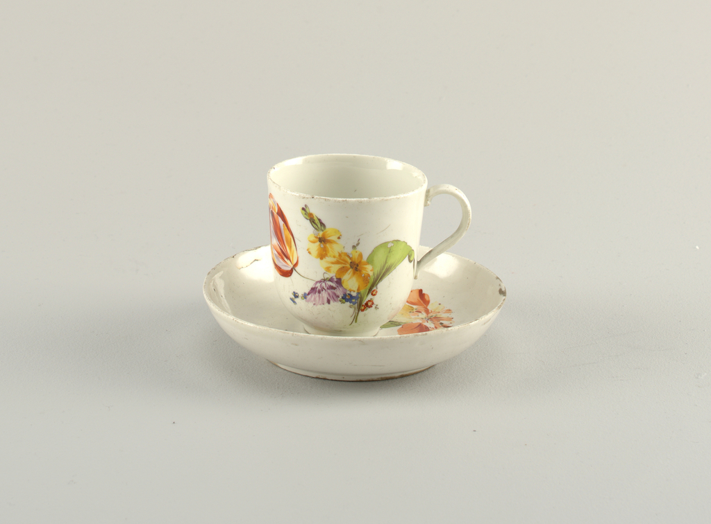 Cup with handle, on a round foot Saucer with high sides. Both painted with naturalistic flowers.
