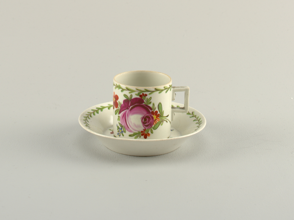 Cylindrical cup; rectangular strap handle, with simulated screw heads. Saucer flat with flaring sides.