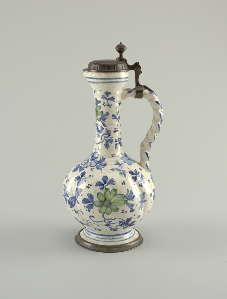 Jug on a spreading circular foot mounted on a pewter ring. The body is bulbous, with a tall neck showing horizontal ribbing, terminating in a flaring mouth and open spout. Braided loop handle. Creamy- white crackled glaze, with underglaze blue and green decoration showing flowers and clustered dots. Flat gadrooned cover mounted on handle.