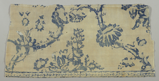 Fragment in two shades of blue on a white ground. Design of undulating branches with large blossoms. Very fine white dots used to enhance design. Separate border in similar design.