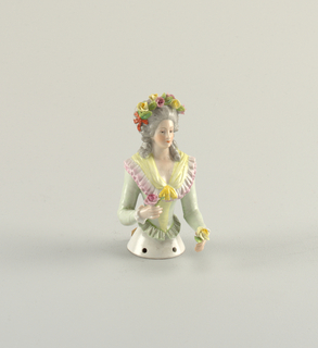 Half figure intended to be made into a pin cushion, representing a woman shown to the waist with flange having three holes to which a skirt may be attached. The woman wears a green bodice, with long sleeves, low cut neck with purple ruffle and yellow scarf, a wreath of flowers in her hair and a rose in each hand.