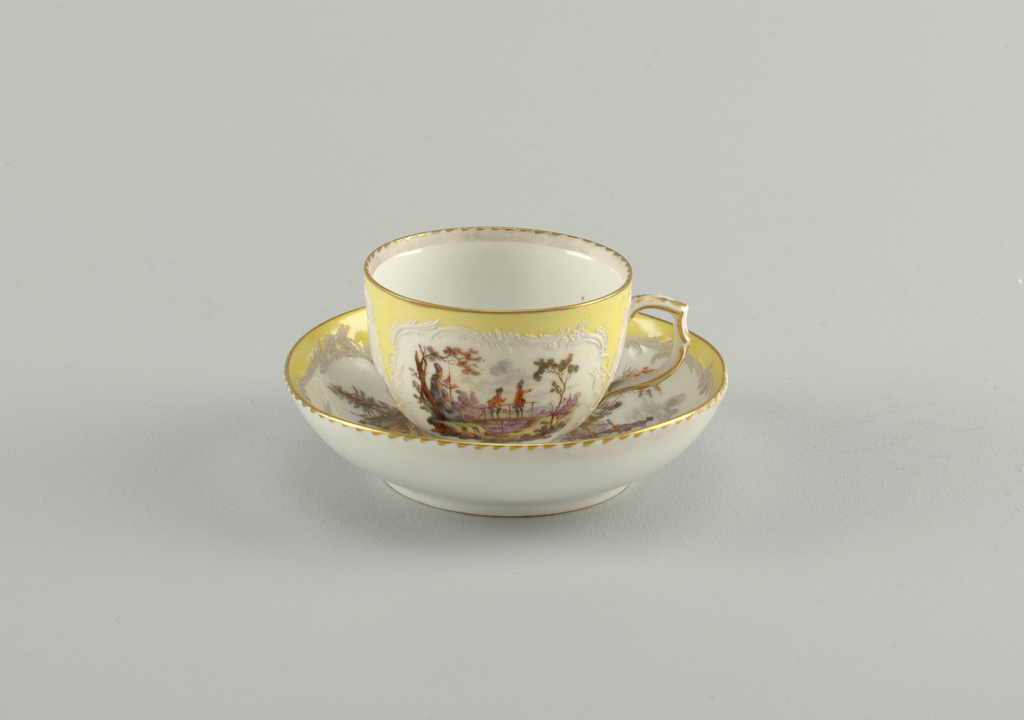 Curving cup. Slightly compressed in lower part. Scrolling handle. Saucer slightly curved. Decoration similar to that of 1953-17-49. Neuzierat style.
