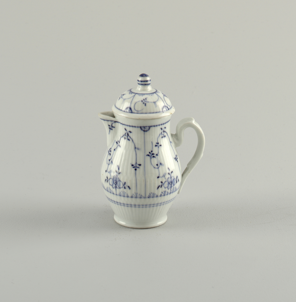 """Pear-shaped body with open spout and strap handle. Dome-shaped cover with round knob. Body and cover reeded and decorated in underglaze blue """"Strohblumen"""" pattern."""
