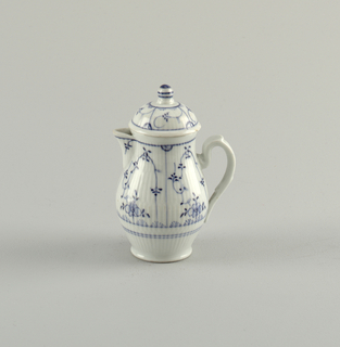 "Pear-shaped body with open spout and strap handle. Dome-shaped cover with round knob. Body and cover reeded and decorated in underglaze blue ""Strohblumen"" pattern."