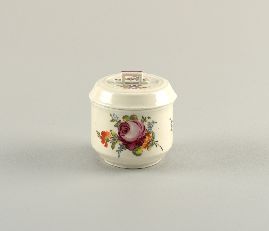 Cylindrical; molded flat cover with rectangular strap handle. Overglaze polychrome decoration of flowers.