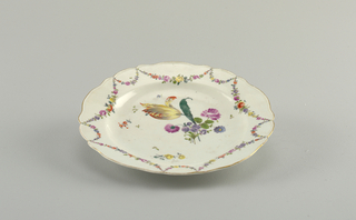 Plate with scalloped edge. Painted in polychrome showing a floral garlands at border. At center, a large floral spray featuring a tulip.