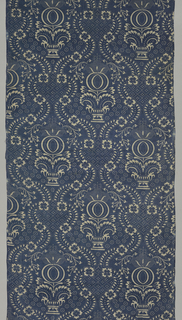 Symmetrical vertical pattern of urns and very stylized flowers in a framing device, with small diaper and floral patterns in the ground, in ivory on indigo blue.