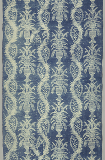 Coverlet or hanging of blue resist with a design of harvest flowers in vases set within ascending curves that carry the grain motif. Two selvages present.