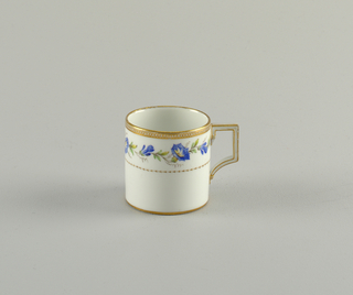 A porcelain cup  with floral pattern in gilding. Angular handle.