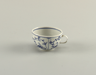 "Curved, with small loop handle. Blueish glaze with blue underglaze decoration showing ""strohblumen"" pattern."