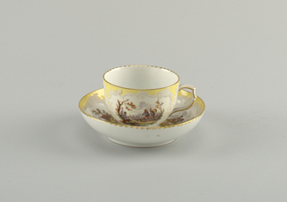 Curving cup. Slightly compressed in lower part. Scrolling handle. Saucer slightly curved. Decoration similar to that of 1953-17-48. Neuzierat style.