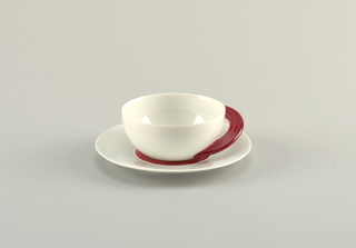 White open bulbous cup with blood red semi-circular handle made of three tubes that reach around side of cup, on a white saucer with blood red center.