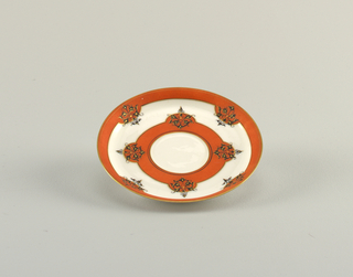 Overglaze and underglaze decoration in colors of American flag, eagels, head of Liberty with decorative borders of orange, gold, and black.
