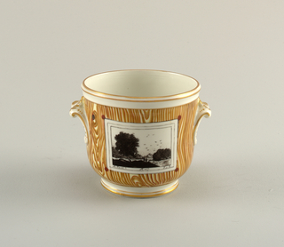 Cylindrical, rounded at bottom and having a cylindrical foot; two outcurving foliate handles on sides. Decorated with brown simulation of wood graining, with reserve rectangular panel decorated in black with simulation of landscape print.
