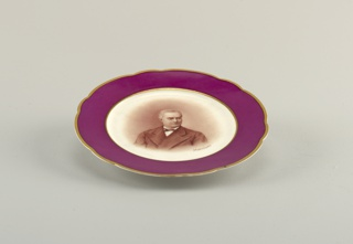 """Circular plate with shaped rim; in the center a portrait of Fyodor Notgaft;a wide band of dark red around border, edged by thin lines of gilding; inscribed under portrait: """"Notgaft"""" (in Russian)"""