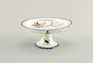 Footed bowl with flower, fish, and grasshopper, bordered by blue.