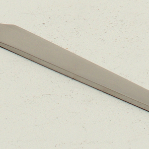 Simple flat one-piece form of shaped blade tapering to curved point at end of handle; matte finish.