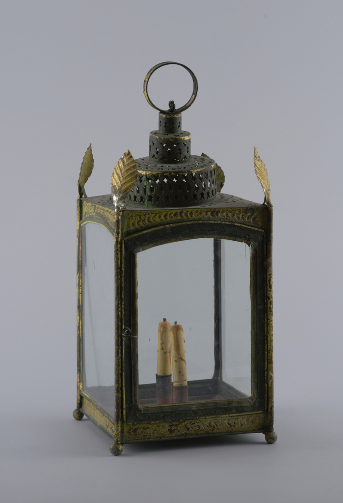 Ebonized and gilded tôle square lantern. Small ball feet and circular stepped top with pierced pattern. At each upper corner, an upright gilded elm leaf. At top, a flat suspension ring. Square bottom inset with two candle holders painted red.