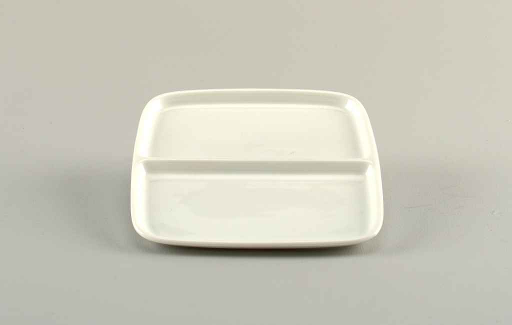 Shallow square form curved at corners, sides slightly out-turned and with rounded lip at top; divided along center to form two rectangular sections; white glaze.