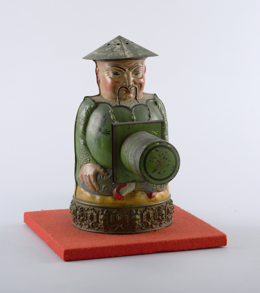 a) Figure of a seated figure in blue-gray trousers and green coat, on circular plinth decorated with masks and shells. Threaded circular opening on belly. b) conical pierced hat. c) tube with square slide holder. d) upainted projector tube, lens missing. e) circular slightly domed cover.