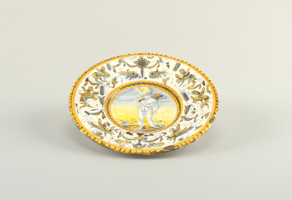 Plate with image of blindfolded Cupid at center. Rim decorated with grotesques. Yellow dash border.