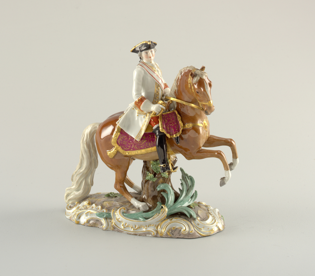 Officer on horseback. On oval base painted to simulate stone, framed by gilt scrolls. A prancing sorrel supported by tree trunk. An officer on white, gold edged coat and black tricorne in saddle, holding sword hilt in front and reigns in left hand.