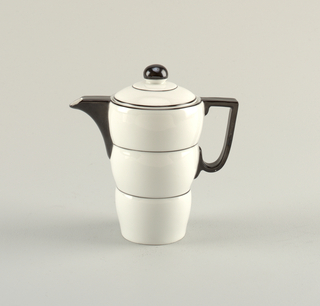 Tall white porcelain coffeepot with thin black bands circling the body; black handle and spout. Lid has black concentric circles and black spherical knob.